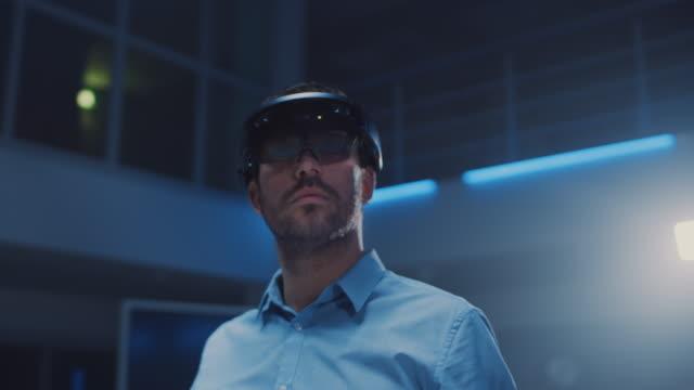 3d içerik oluşturmak laboratuvar mühendisi profesyonel sanal gerçeklik kulaklık işleri ve augmented gerçeklik jestleri giyiyor. şık düşük açılı yay portre çekimi - sanal gerçeklik stok videoları ve detay görüntü çekimi