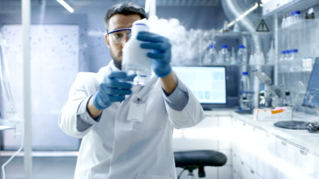In a Chemical Research Laboratory Scientist Mixes Smoking Compounds in Beakers. video