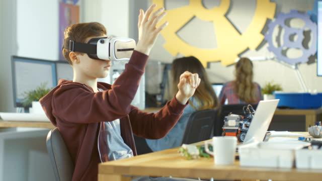 In einem Computer Wissenschaft Klasse jungen tragen Virtual-Reality-Kopfhörer funktioniert auf Programmierung Gesten für das Projekt. – Video