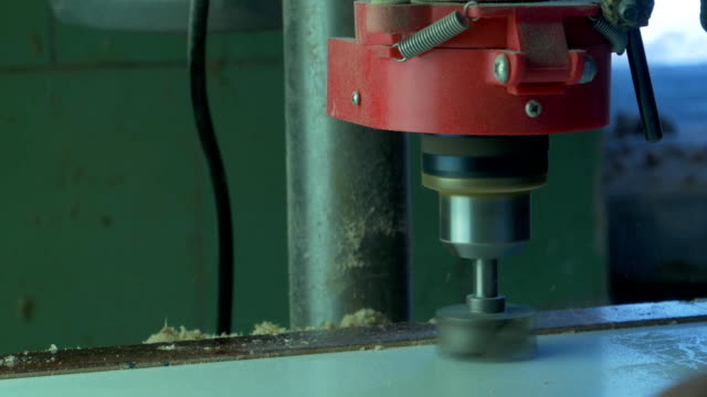 In a furniture factory, a man drills holes for furniture hinges. Drill Forstner. Forstner bit drilling into soft wood, closeup video