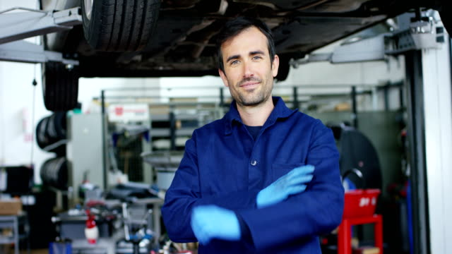 vídeos de stock e filmes b-roll de in a garage a mechanic using the tablet makes the oil and engine check to the car smiles. - fundo oficina