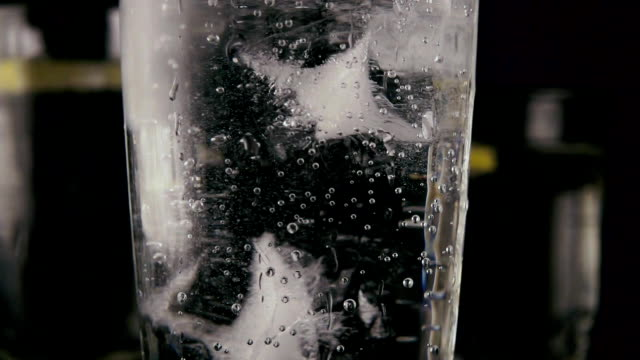 In a glass with a soda throw ice. Slow motion In a glass with a soda throw ice in the background glasses with water and lemon. Slow motion tonic water stock videos & royalty-free footage