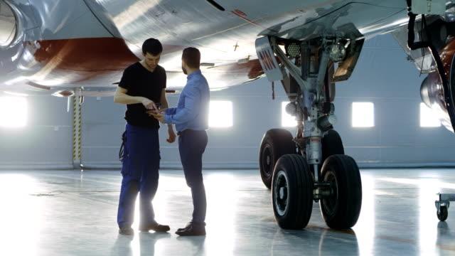 格納庫航空機メンテナンス エンジニア ショー技術データ飛行機技術者にタブレット コンピューター上で。彼らはきれいなブランド新しい平面の近くに立っています。 ビデオ