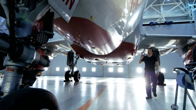 In a Hangar Aircraft Maintenance Engineer/ Technician/ Mechanic Visually Inspects Airplane's Chassis and Body/Fuselage walking Under It. video