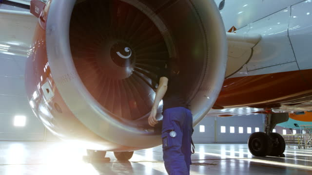 In a Hangar Aircraft Maintenance Engineer/ Technician/ Mechanic Inspects with a Flashlight Airplane's Jet Engine. video