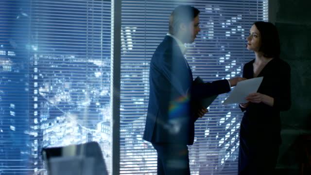 vídeos de stock, filmes e b-roll de em um escritório privado moderno jovem masculino e feminino sucesso start-up parceiros têm discussão sobre contratos importantes. o escritório tem a janela com opinião grande da cidade. - países bálticos