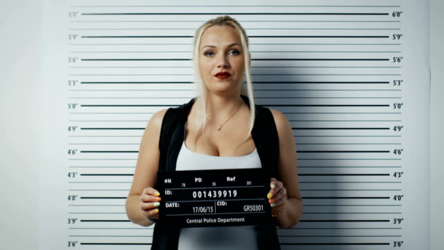 In a Police Station Arrested Woman Steps in and Gets Side, Front-View Mug Shot. She Wears Saucy Clothes, Has Heavy Makeup and Holds Placard. Height Chart in the Background. video