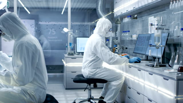 in a secure high level laboratory scientists in a coverall conducting a research. biologist adjusts samples in a  petri dish with pincers and then examines them under microscope and his colleague analyzes results on a computer. - contagi video stock e b–roll