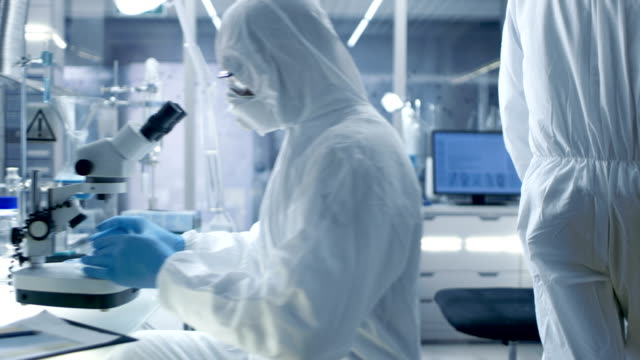 In a Secure High Level Laboratory Scientists in a Coverall Conducting a Research. Biologist Adjusts Samples in a  Petri Dish with Pincers and then Examines Them Under Microscope and His Colleague Analyzes Results on a Computer. video