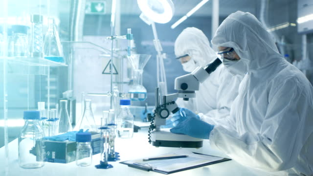 In a Secure High Level Laboratory Scientists in a Coverall Conducting a Research. Chemist Adjusts Samples in a  Petri Dish with Pincers and then Examines Them Under Microscope and His Colleague Writes Down Results. video