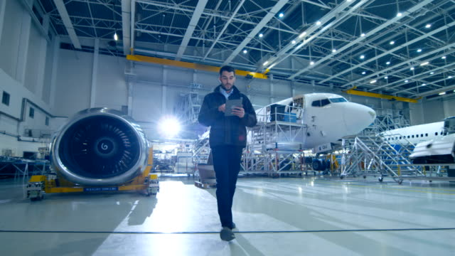 In Aircraft Designing Facility Chief Engineer Walks Through Hangar Used Digital Tablet Computer in the Background Modern Passenger Airplane  with Prototype Wing and Engine Parts