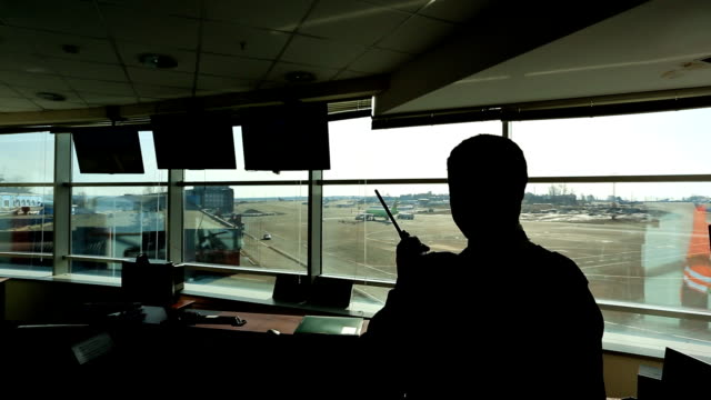 In airport air traffic controller is looking into distance holding radio video