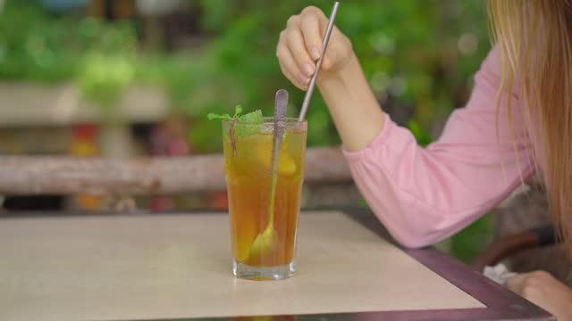 i ett miljövänligt café dricker en ung kvinna ett kallt te med ett återanvändbart stålstrån. koncept för att minska användningen enda plast - sugrör bildbanksvideor och videomaterial från bakom kulisserna
