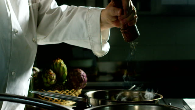 in an italian professional kitchen a chef pours salt on a dish or in the water to boil the italian pasta concept of healthy and light food. - salt video stock e b–roll