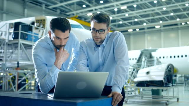 큰 공항 시설 격납고 2 influencial 투자자 들이 노트북 컴퓨터를 사용 하 여 토론을 하 고 있습니다. 항공사 담당자가 작업을 최적화 합니다. 백그라운드에서 비행기와 엔진 - 항공 비행체 스톡 비디오 및 b-롤 화면