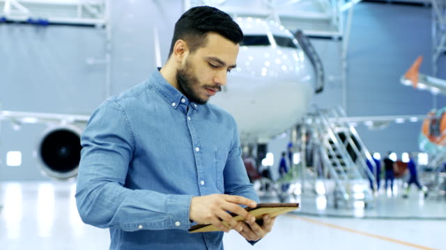 In Big Company Hangar Aircraft Maintenance Engineer Uses Tablet Computer while Standing Near Big New Shiny White Plane. video