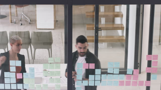 In business you keep up or get left behind 4k video footage of two young businesspeople writing notes and brainstorming ideas on a glass wall inside their office coworking stock videos & royalty-free footage
