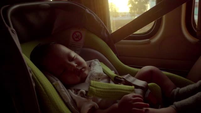 i bilsäkerhet för barn. liten pojke som sitter i en särskild bilbarnstol - baby sleeping bildbanksvideor och videomaterial från bakom kulisserna