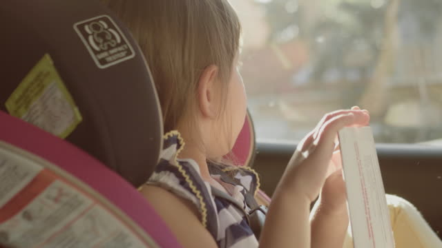 In car safety for children. Little girl sitting in a special car seat