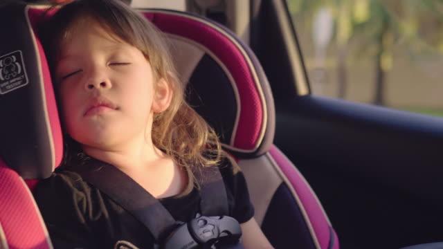 子供のための車の安全性。特別な車の座席に座っている少女 - 楽しい点の映像素材/bロール