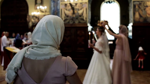 In church orthodox woman cross blessing herself with fingers and bow watching wedding ceremony view from back. Greek orthodox church rituals traditions customs. Religious people cult worship concept video