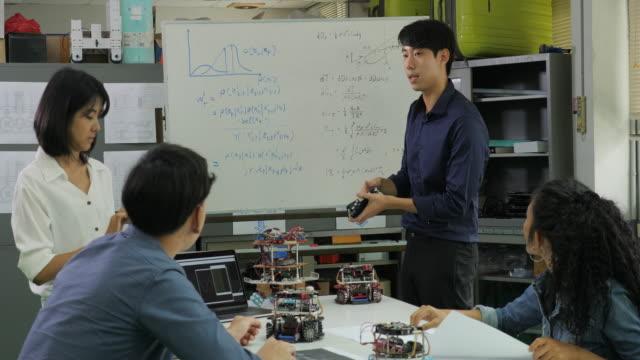 コンピューター科学クラスの教師ロボット技術について学生に話します。男性エンジニア チームと現在のプロジェクト。技術または技術革新の概念を持つ人々。 - 研修点の映像素材/bロール