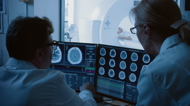 in control room doctor and radiologist discuss diagnosis while watching procedure and monitors showing brain scans results, in the background patient undergoes mri or ct scan procedure. - radiografia video stock e b–roll