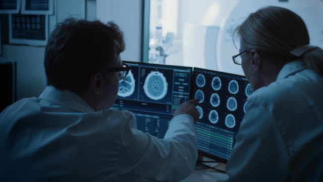 In Control Room Doctor and Radiologist Discuss Diagnosis while Watching Procedure and Monitors Showing Brain Scans Results, In the Background Patient Undergoes MRI or CT Scan Procedure. In Control Room Doctor and Radiologist Discuss Diagnosis while Watching Procedure and Monitors Showing Brain Scans Results, In the Background Patient Undergoes MRI or CT Scan Procedure. Shot on RED EPIC-W 8K Helium Cinema Camera. diagnostic medical tool stock videos & royalty-free footage