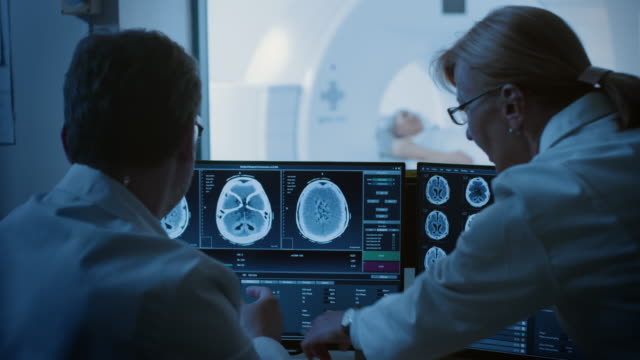 In Control Room Doctor and Radiologist Discuss Diagnosis while Watching Procedure and Monitors Showing Brain Scans Results, In the Background Patient Undergoes MRI or CT Scan Procedure. In Control Room Doctor and Radiologist Discuss Diagnosis while Watching Procedure and Monitors Showing Brain Scans Results, In the Background Patient Undergoes MRI or CT Scan Procedure. Shot on RED EPIC-W 8K Helium Cinema Camera. radiologist stock videos & royalty-free footage