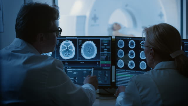 In Control Room Doctor and Radiologist Discuss Diagnosis while Watching Procedure and Monitors Showing Brain Scans Results, In the Background Patient Undergoes MRI or CT Scan Procedure. In Control Room Doctor and Radiologist Discuss Diagnosis while Watching Procedure and Monitors Showing Brain Scans Results, In the Background Patient Undergoes MRI or CT Scan Procedure. Shot on RED EPIC-W 8K Helium Cinema Camera. oncology stock videos & royalty-free footage