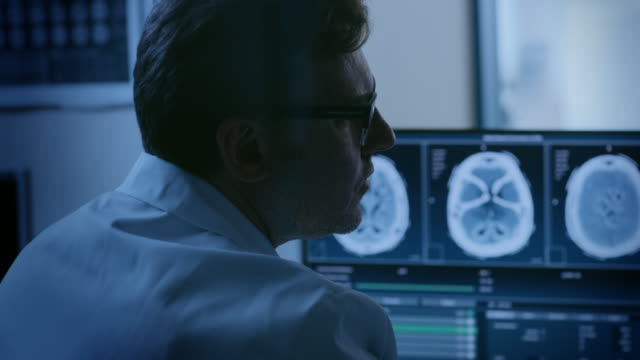 vídeos de stock e filmes b-roll de in control room doctor and radiologist discuss diagnosis while watching procedure and monitors showing brain scans results, in the background patient undergoes mri or ct scan procedure. - clínica médica