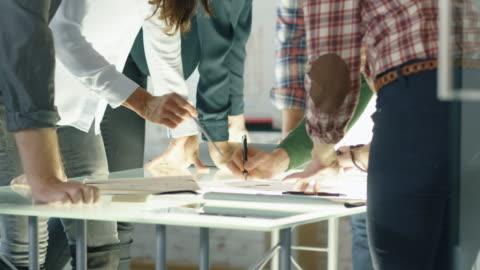 vídeos y material grabado en eventos de stock de en la oficina creativa. cierre disparo de una mesa de conferencia de vidrio ocupado y compañeros de trabajo apoyándose en él en colectivo salto a encontrar soluciones problemáticas. - ideas