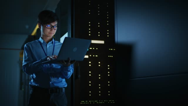 in dark data center: male it specialist stands beside the row of operational server racks, uses laptop for maintenance. concept for cloud computing, artificial intelligence, supercomputer, cybersecurity. neon lights - criptovaluta video stock e b–roll
