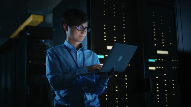 In Dark Data Center: Male IT Specialist Stands Beside the Row of Operational Server Racks, Uses Laptop for Maintenance. Concept for Cloud Computing, Artificial Intelligence, Supercomputer, Cybersecurity. Neon Lights video