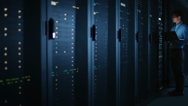 i mörka data center: hane it specialist står bredvid raden i operativa serverrack, använder laptop för underhåll. koncept för cloud computing, artificiell intelligens, superdator, cybersäkerhet. neonljus - server room bildbanksvideor och videomaterial från bakom kulisserna
