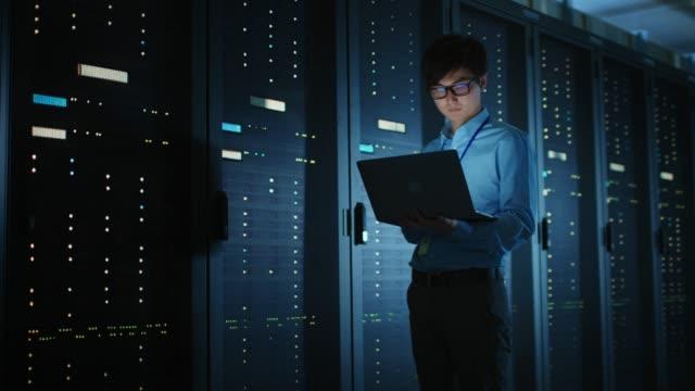 i mörka data center: hane it specialist promenader längs raden med operativa serverrack, använder laptop för underhåll. koncept för cloud computing, artificiell intelligens, superdator, cybersäkerhet - server room bildbanksvideor och videomaterial från bakom kulisserna
