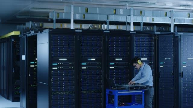 i datacenter: ingenjör det bär skyddande kåpor installerar ny maskinvara för serverrack. specialist göra underhåll, kör diagnostik och uppdatera maskinvara för stabil funktion i ett system. - server room bildbanksvideor och videomaterial från bakom kulisserna