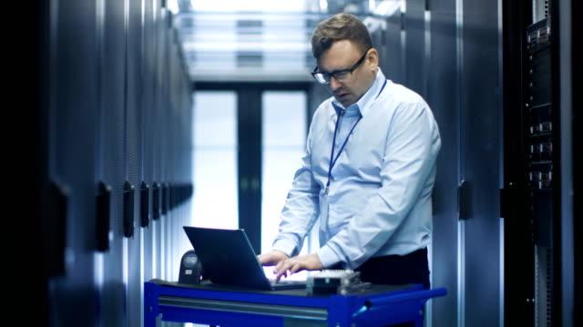 stockvideo's en b-roll-footage met gegevens centreren ingenieur werkt op crash cart laptop. we zien rijen van server racks en een kabinet is open. - datacenter