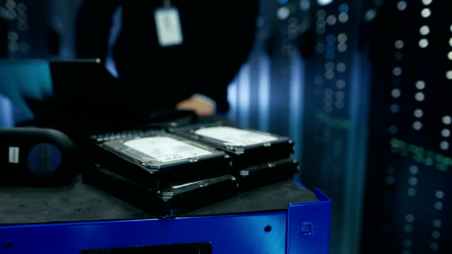 In Data Center IT Technician Pushes Crash Cart With Various Hardware and Laptop on It. video