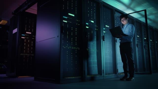 stockvideo's en b-roll-footage met in datacenter: man it technicus running onderhoudsprogramma op een laptop, besturingselementen operationele server rack dat optimale werking. moderne high-tech telecommunicatie operationele super computer. - datacenter