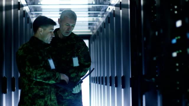 データセンターでは、2人の軍人がオープンサーバーラックキャビネットで作業しています。1つは軍事版ラップトップを保持します。 - デイフェンス点の映像素材/bロール