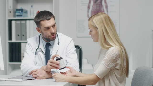 In Doctor's Office. Practicing Doctor Gives Prescribed Bottle of Pills to His Beautiful Blond Female Patient. video