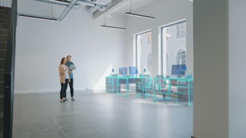 vidéos et rushes de dans empty new office: female interior designer et male office architect talk, utilisez le logiciel de réalité augmentée sur l'ordinateur tablette numérique pour choisir, déplacer et manipuler les meubles 3d. rendu vfx - bureau ameublement