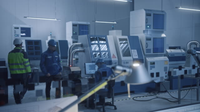 In Factory: Professionals Working on CNC Machinery Walk Through Workshop, Use Digital Tablet Manipulate Robot Arm Production Line. In-Office: Male Engineer Controls System mit Computer. Bewegte Kamera – Video