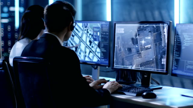 In Government Agency System Surveillance Center Employees Trace Criminal with Help of GPS. They Room is Full of Displays with Various Data on Them. video