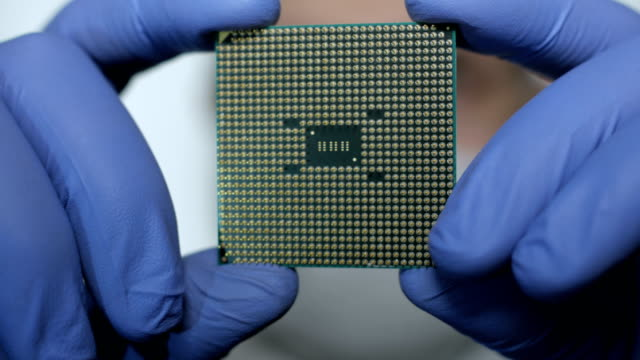 技術者の手で cpu。プロセッサは、見かけ上の不具合のため検討中です。現代の電子機器受託製造工場設計エンジニアを保持マイクロ チップ。クローズ アップ新世代マイクロ チップ。 - 半導体点の映像素材/bロール