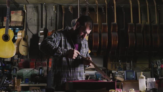 In his laboratory, a liutist builds high quality guitars for musicians, working fine wood.