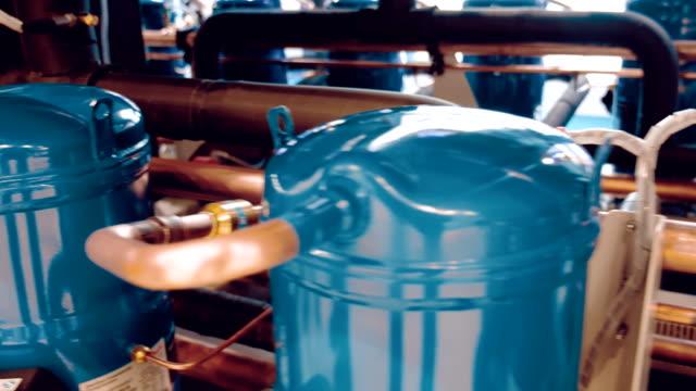 i industriell utrustning, är kopparrör anslutna till blå metall cylindrar - värmepump bildbanksvideor och videomaterial från bakom kulisserna