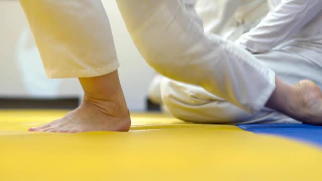 in kimono sitting on tatami of martial arts. video