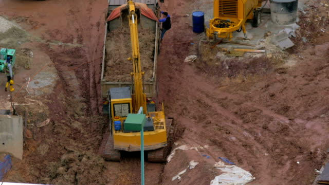 In Kuala Lumpur, Malaysia in the pit excavator pours earth into a truck video